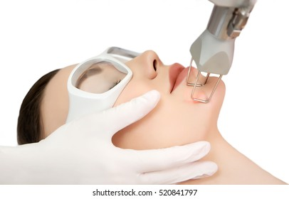 Therapist beautician makes a  laser rejuvenation for the model by  apparatus  in a beauty salon.  Close up, selective focus.