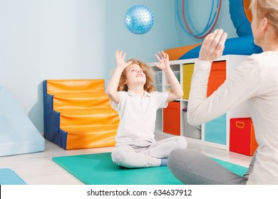 Therapist and boy playing ball during senory therapy
