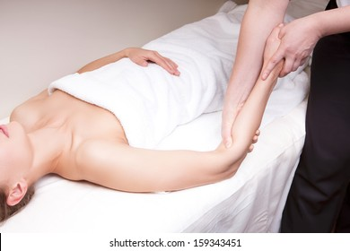 A therapist doing deep tissue massage on a woman's forearm
