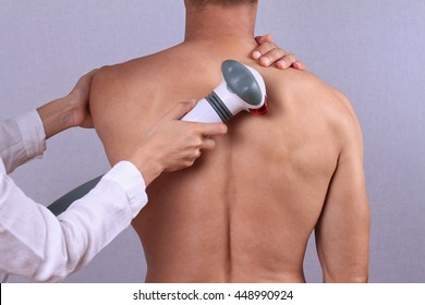 Therapist doing healing infrared treatment on man's back . Alternative medicine, physiotherapy, pain relief concept