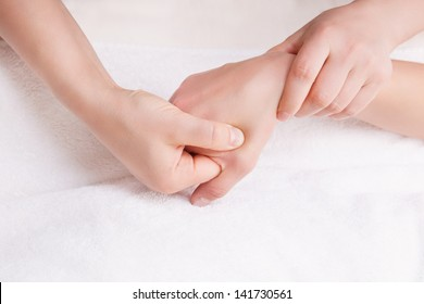 Therapist doing a pressure point massage on the woman's right hand