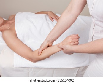 Therapist doing therapeutic deep tissue massage on muscles of a woman's  forearm