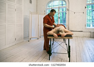 Therapist during moxibustion therapy for female patient. Horizontal shot