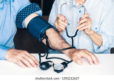The therapist female hands with a classic tonometer measuring blood pressure of an man in home room on white table