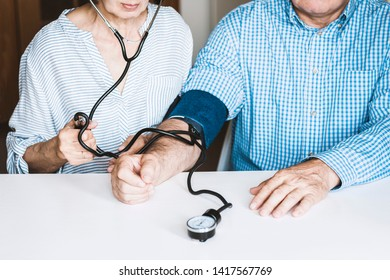 The therapist female hands with a classic tonometer measuring blood pressure of an man in blue shirt in home room on white table