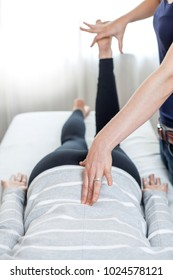 Therapist giving Kinesiology treatment in bright white room.
