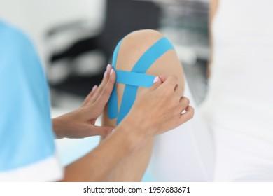 Therapist gluing blue kinesio tapes on woman sore knee closeup