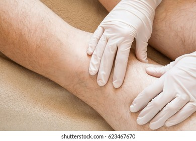 Therapist hands in protective gloves massaging man's legs.