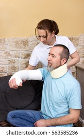 An therapist helps a injured man in rehabilitation