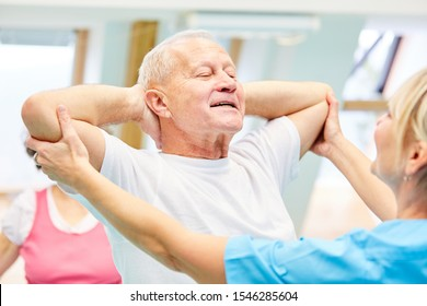 Therapist helps senior man with healthy back training in the rehab clinic
