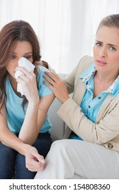 Therapist with her patient crying on couch in office