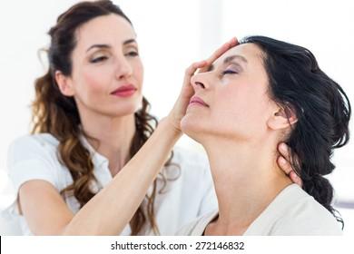 Therapist hypnotizing her patient on white background