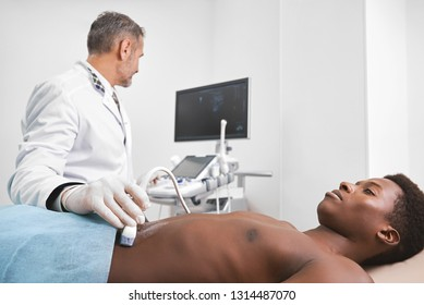 Therapist looking at screen of monitor, holding device and doing ultrasound diagnosis of man's belly. African patient lying with naked torso. Doctor wearing in medical white gown.