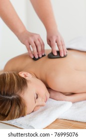 Therapist making a massage to an attractive blond-haired woman in a spa center