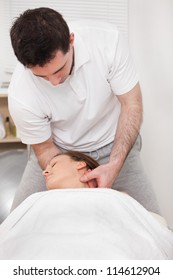 Therapist manipulating the neck of his patient while standing in a room