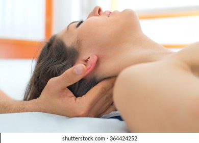 Therapist massaging the neck of woman In the studio