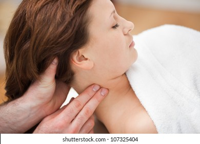 Therapist massaging the neck of woman while holding her head in a room