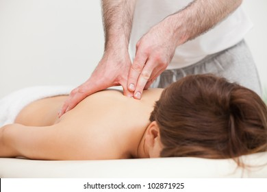 Therapist massaging the top of back of woman while standing in a room