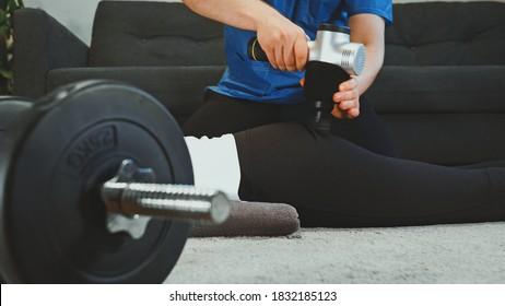 Thérapeute massant les jambes de la femme avec appareil de massage à percussion chez elle.