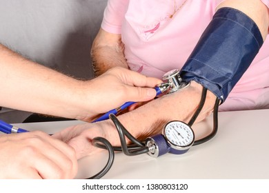 The therapist measures blood pressure of an elderly woman with a classic tonometer in office.
