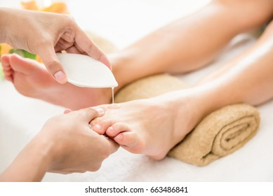Therapist pouring oil to a woman foot about to massage