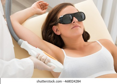 Therapist Removing Hair Of Young Woman's Armpit In Cosmetic Beauty Clinic