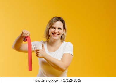 A therapist rolling kinesiology tape to demonstrate it on the yellow background. Alternative kinesio tape therapy, healthcare concept