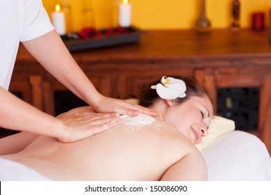 Therapist in a spa cleansing the skin of a beautiful with a salt treatment to exfoliate dead cells and energise with marine minerals