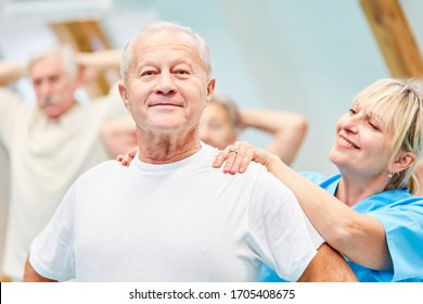 Therapist supports senior man in healthy back training