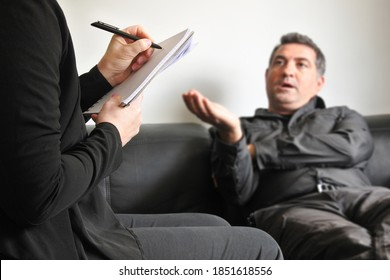 Therapist taking notes during a conversation with mature adult businessman patient (age 40-50) suffering from mental stress, anxiety, fear, anger, sadness, frustration in psychologist clinic.
