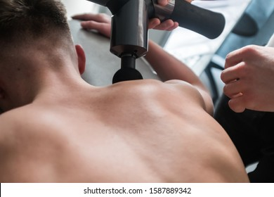 Therapist Treating Injury of Professional Athlete Male Patient. Black Massage Gun, Used by Professionals to Massage the Body.Sport Physical Therapy Concept. - Photography
