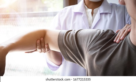 Therapist treating a male injured by shoulder impingement test, Physical therapy concept.