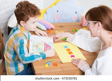 Therapy session with the therapist teaching the young boy alphabet