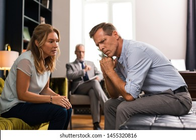 Therapy together. Calm wife talking to her husband during the session in the presence of a psychologist