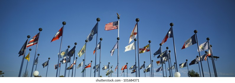 There are 50 State Flags waving in the wind on flagpoles equal distant apart against a blue sky, with the American flag in the center.