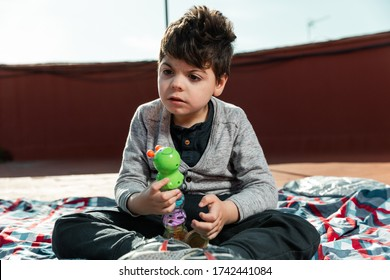 There is a 5-year-old boy playing on the terrace of a house with a plastic, rattle-like, green worm-like toy. the child suffers from physical and intellectual disabilities.
