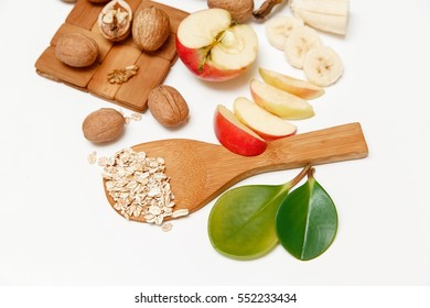 There are Banana,Apple,Walnuts and Rolled Oats,Wooden Spoon,Trivet,with Green Leaves,Healthy Fresh Organic Food on the White Background,Top View