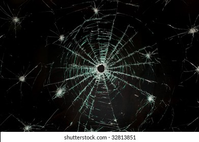 There is a broken car glass of windscreen with hole in picture center