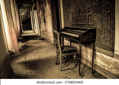 There is a chair and a piano in a dark decrepit place.