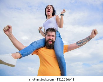 There is chemistry between them. Bearded man piggybacking his girlfriend just for fun. Hipster giving sexy woman a piggyback ride. Happy couple in love on cloudy sky. Loving couple smile having fun.