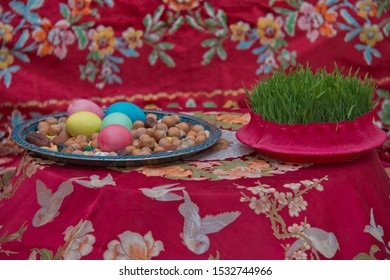 There are colored eggs, hazelnuts, dates, and peanuts in the cabin. Novruz symbol on xoncha on white background Azerbaijan holiday . Green semeni .