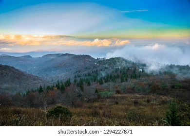 There are colorful sunset cloud formations over this beautiful Autumn Smoky Mountain scene on the Blue Ridge Parkway in North Carolina. Beautiful evergreens dot the mountainsides..