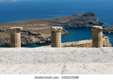 There are columns in the ancient Acropolis in Lindos, Rhodes, against the blue sea.