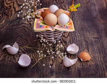 There are egg shells l with easter basket and flowers on the wood texture