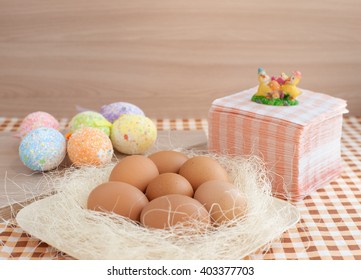 There are a lot of eggs on the table. Decorative eggs for Easter. Eggs on the straw in a rustic style. A lot of paper napkins and eggs on the table.