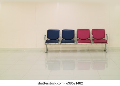 There are four blue and pink chairs in a room with gray walls and floor. Concept of a waiting area.