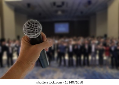 There is a hand hold a microphone ready to speak before many people in seminar event