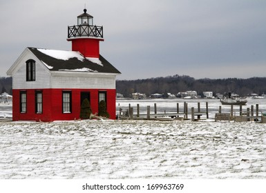 There is little activity at the Kalamazoo River Lighthouse. An old tug boat sits stranded in the icy river during the early part of winter. Saugatuck, Michigan, USA.