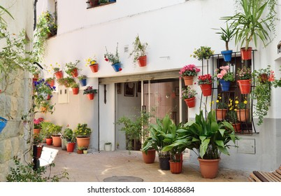 There are many flowerpots with blooming plants near and on the stone wall of houses in the Spanish town.