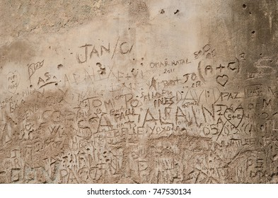 There are many symbols, letters and words scratched on the cement wall.